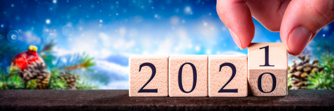 Hand Changing Date From 2020 To 2021 On Wooden Cube Calendar / New Year's Concept