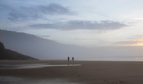 A far off view of two people walking on a foggy beach at sunset - Cape Lookout Beach, Oregon