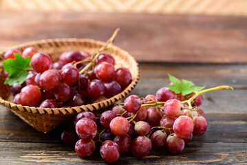 Fresh red grapes fruit in a basket on wooden background