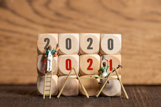 little painter figures and message 2020, 2021 on wooden cubes in front of wooden background
