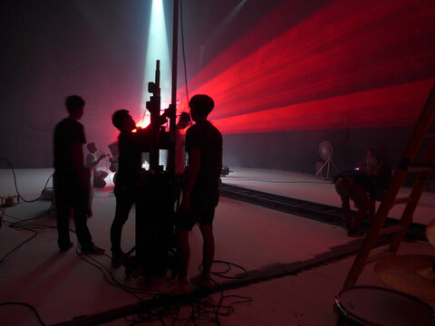 Blurry image and out of focus : Behind the scenes of video shooting production crew team silhouette and camera equipment in studio, Red laser light beam