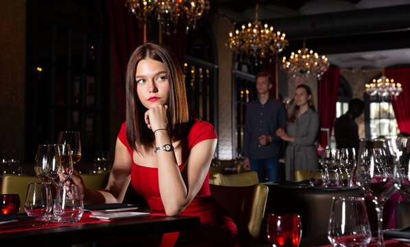 Portrait of beautiful young woman with glass of wine sitting in restaurant