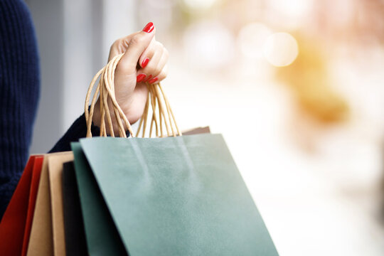 Closeup of woman hand holding shopping bag colorful paper on the street happy summer with copy space.