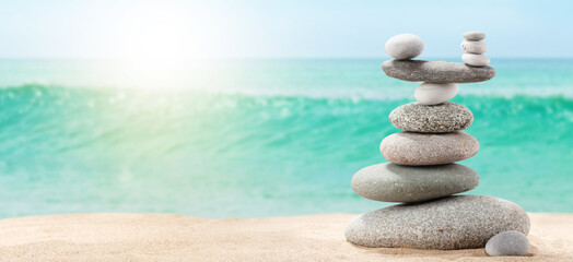 Pyramid of sea pebbles on a sunny sand beach
