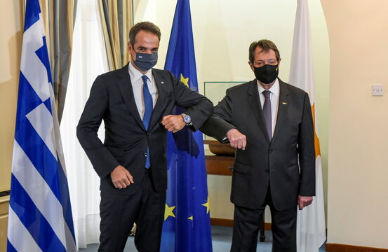 Cypru's President Nicos Anastasiades and Greece's Prime Minister Kyriakos Mitsotakis bump their elbows before a trilateral summit between Greece, Cyprus and Egypt, at the Presidential Palace in Nicosia