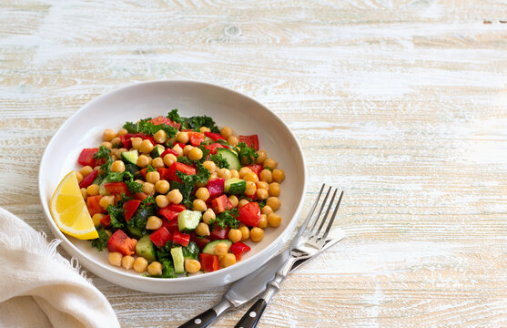 Healthy vegan salad with chickpeas, tomatoes, cucumbers, bell peppers and kale on light wooden background, space