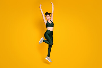 Full size photo of sportive lady jump high up active person raise arms wear sports suit sneakers...