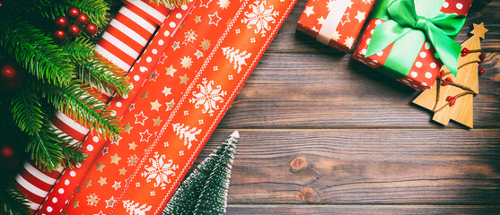 Wall Mural - Top view of Christmas background made of fir tree, rolled wrapping paper and other decorations on wooden background. Banner New Year holiday concept with copy space