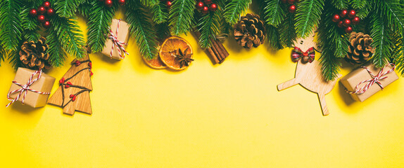 Wall Mural - Top view of Christmas decorations on yellow background. Banner New Year holiday concept with copy space
