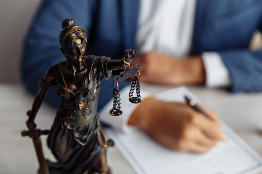 Lawyer office. Statue of Justice with scales close-up and lawyer. Legal law, advice and justice concept.