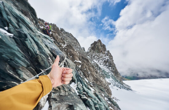 Close up of alpinist hand doing approval gesture with rocky mountains and sky on background, showing thumbs up sign while friend climbing winter mountain. Concept of approval and travelling.
