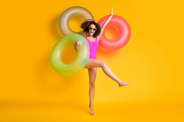 Photo sur Plexiglas Dinosaurs Photo portrait of excited girl standing on one leg wearing pink swim wear holding green red blue inflatable ring isolated on vivid yellow colored background