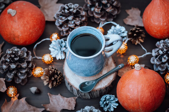 Mug with hot coffee and dry leaves, pumpkins, cones on wooden table, autumn lifestyle