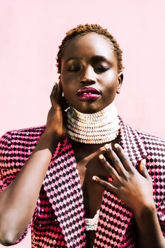 Beautiful African model with black skin against a pink background. Authentic smile. Vibrant colours, candy necklace