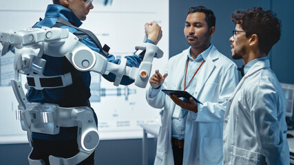 In Robotics Development Laboratory: Engineers and Scientists Work on a Bionics Exoskeleton Prototype with Person Testing it. Designing Wearable Exosuit to Help Disabled People.