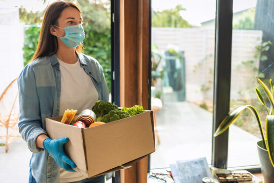Young woman isolated received delivery of cardboard box with groceries to the front door. Donation or online food delivery concept
