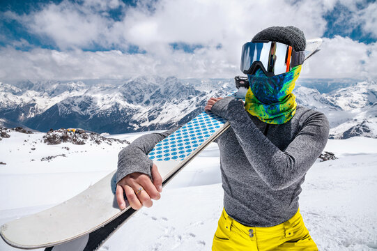 Portrait of a slender young woman in a ski mask in the mountains without a jacket in winter with skis on her shoulder against the background of snow-capped peaks on a sunny day high in the mountains