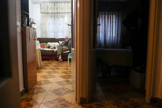 Florentina Martin, a 99 year-old woman who survived coronavirus disease (COVID-19), sits on a sofa with her pet Luna as she watches TV at her home in Pinto
