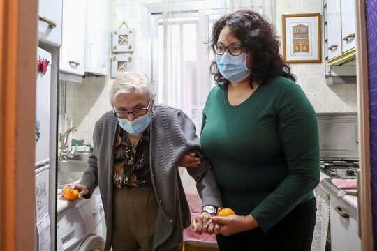 Florentina Martin, a 99 year-old woman who survived coronavirus disease (COVID-19), is helped by her caregiver Olga Arauz in her home in Pinto