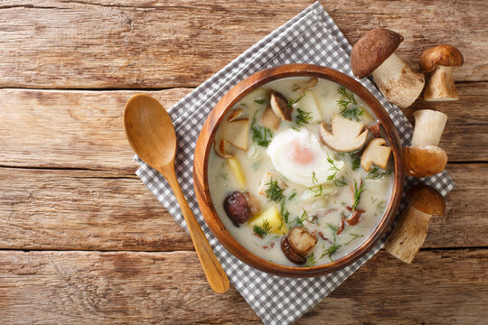 Kulajda is a Traditional Czech white soup full of flavors. This classic recipe contains mushrooms, potatoes, egg and dill close-up in a bowl on the table. Horizontal top view from above