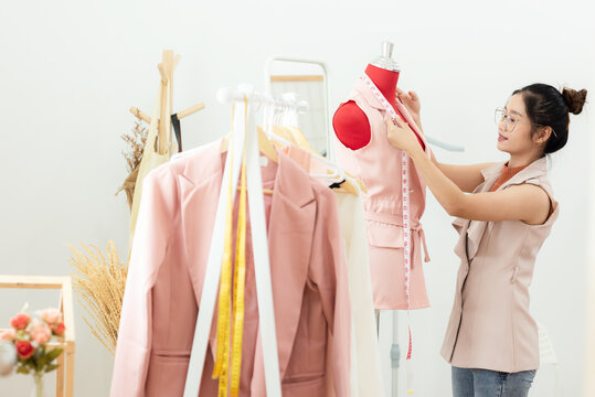 Work from home. Asian young woman fashion designer  working on her design in the showroom.  Lifestyle people Stylish tailor taking measurements on mannequin in studio.