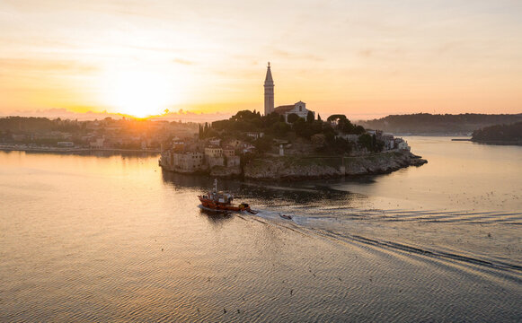 A fishing boat passes by the old town of Rovinj during sunrise