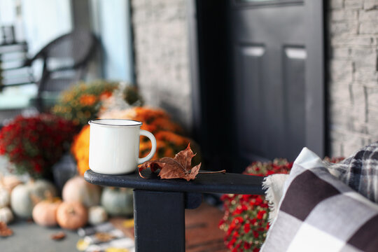 Steaming coffee cup sitting on arm of rocking chair on a front porch that has been decorated for autumn with heirloom white, orange and grey pumpkins and mums. Selective focus with blurred background.