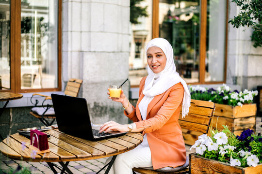 Beautiful young arabic girl in hijab working at street cafe.