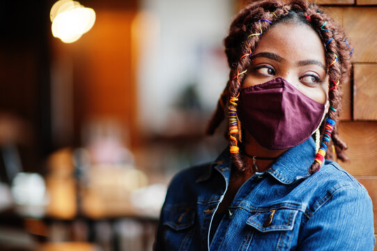Stylish african american woman with dreadlocks afro hair, wear jeans jacket and face protect  mask at restaurant. New normal life after coronavirus epidemic.
