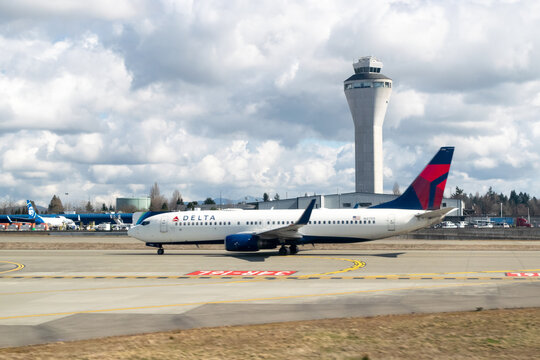 A Delta Airlines Boeing 737 taxis in front of the air traffic control tower at Seattle-Tacoma International Airport (SeaTac) - Seattle, Washington, USA