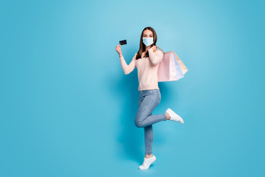 Full length view of girl jumping carrying new things credit card wear mask isolated shine vibrant blue color background