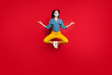Full length photo of calm focused girl jumping sitting lotus pose meditating wear mask isolated bright red color background