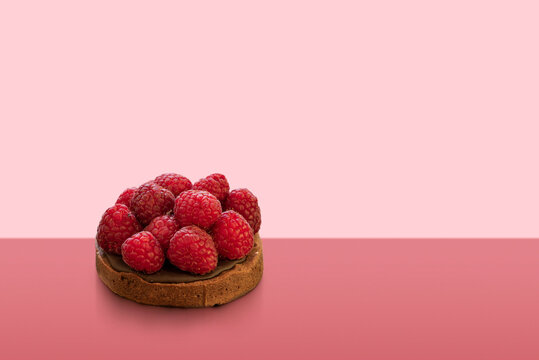 mini chocolate cake decorated with raspberries on colorful background