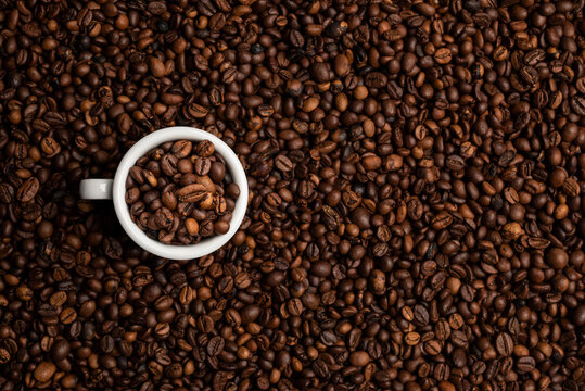 cup full of coffee beans over a background of coffee beans