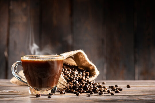 glass cup full of steamed coffee on wooden background with coffee beans