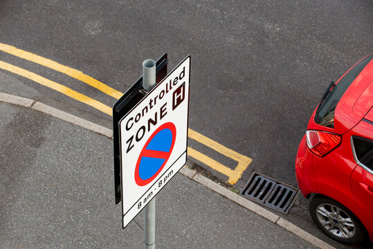 UK. 2020. Roadsign for a controlled zone, no parking between 8am and 8pm. No waiting and double yellow lines.