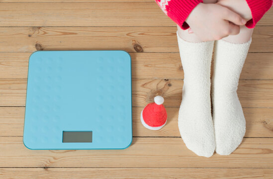 Female feet near  blue electronic scales for weight control  with Christmas santa hat on wooden floor
