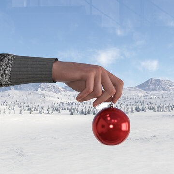 Illustration of a hand holding a red Christmas ornament in front of a window with a snowscape in the background.