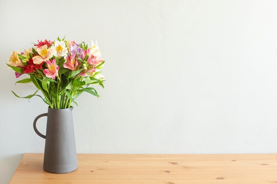 Colorful flowers in a cement vase on a wooden table with copyspace