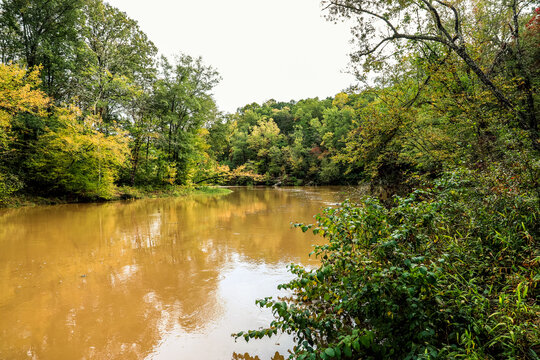 a stunning shot of the deep brown waters of the river with lush green and autumn colored trees on the banks of the Chattahoochee river at Sweetwater Creek State Park in Lithia Springs Georgia