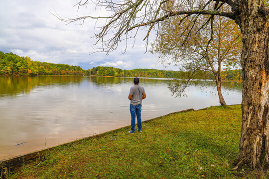 a black man in jeans standing on the banks of the lake flying a drone with lush green and autumn colored trees on the banks of the lake and green grass at Sweetwater Creek State Park in Lithia Springs