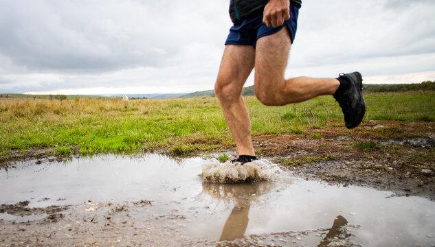 feet of trail runner running in nature