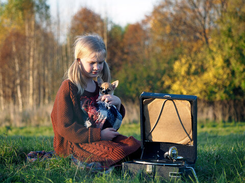 Autumn portrait of a girl with a dog and a gramophone
