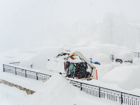 Snow plow tractor and other vehicles heavily covered with snow in a parking lot during a snowstorm