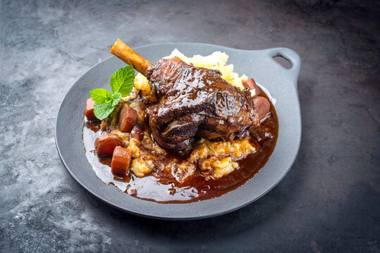 Modern style traditional braised slow cooked lamb shank in red wine sauce with shallots and mashed potatoes offered as top view in a design cast iron plate with copy space