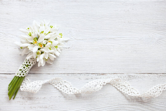 Bouquet of snowdrops, lace ribbon on an old white wooden background, space for text congratulations