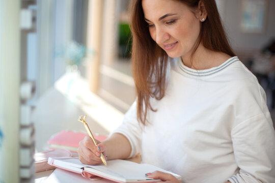 Cheerful young woman writing and keeping her personal a daily diary books.