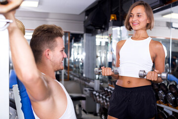 Glad woman training hands using weight dumbbells while talking to friend in gym indoors