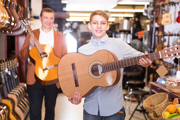 Man and a boy show branded acoustic guitars in a music store