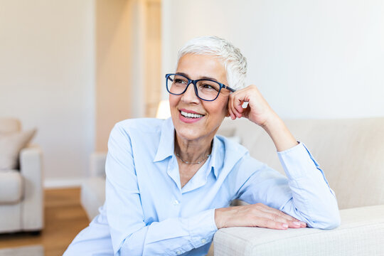 Senior woman looking at camera. Successful mature business woman wearing eyeglasses. Happy old professor in standing in college library with gray hair.